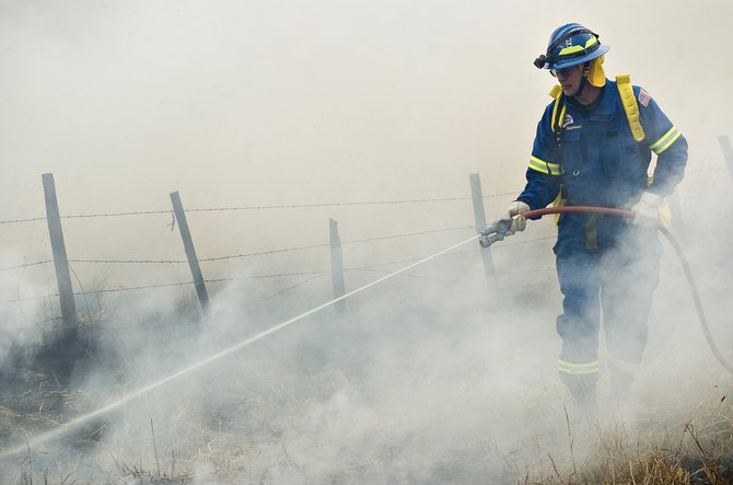 North Routt Fire Protection District volunteer Doug Person uses a small booster line to control a grass fire burning near Clark on Tuesday.  The fire, which spread across five acres with the help of a gusty afternoon wind, burned ranch fields but did not threaten any lives or property.