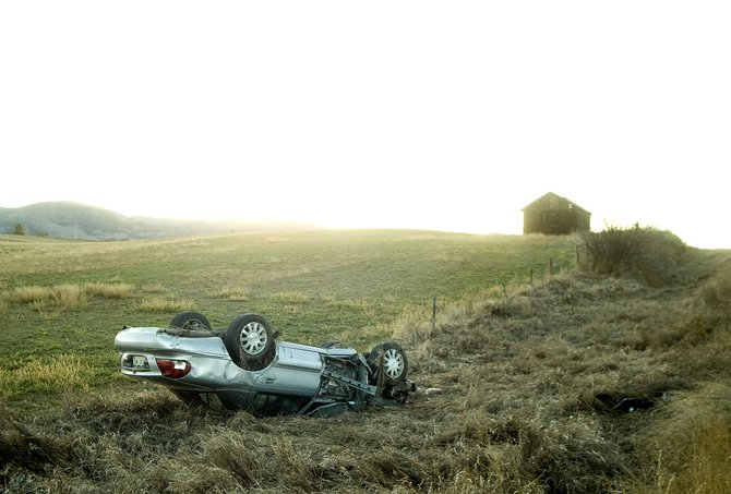 A silver sedan sits overturned in a field off Routt County Road 14 after the driver crashed while leading Colorado State Patrol on a high-speed chase south of Steamboat Springs on Friday evening.