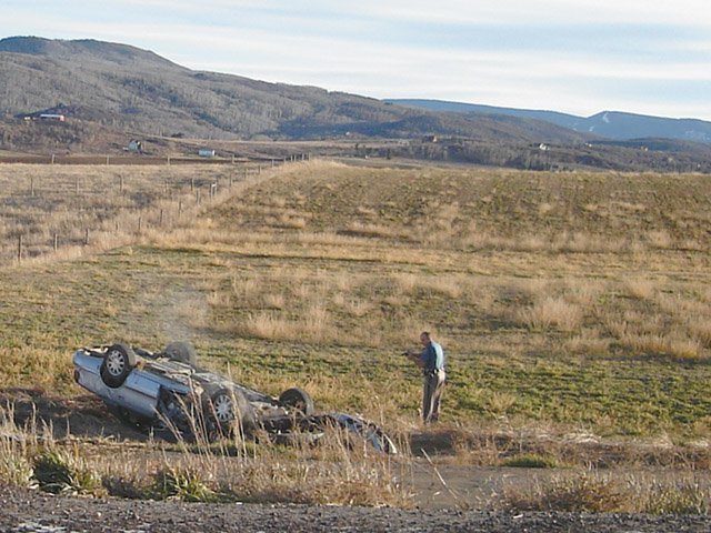 A Colorado State Patrol trooper approaches the vehicle that crashed off Routt County Road 14 after a high-speed chase Friday. The driver of the vehicle walked out of the hospital Saturday morning, and troopers aren't sure of his real identity.