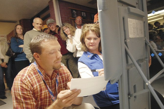 Election judges, Mason Siedschlaw, left, and Lila Herod, right, write down some of the final tallies for Tuesday night's election in front of a crowd of onlookers in the Moffat County Court House in Craig. Both Referendums 1A, which will help pay for construction of a new hospital, and 3A, which will pay for a hybrid middle school and updates to other district schools, passed.