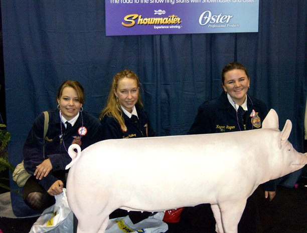 Kacie Owens, Teren Wilkey and Kaycee Stagner pose with a cardboard pig at the Showmaster/Oster Booth at National FFA Convention in October.
