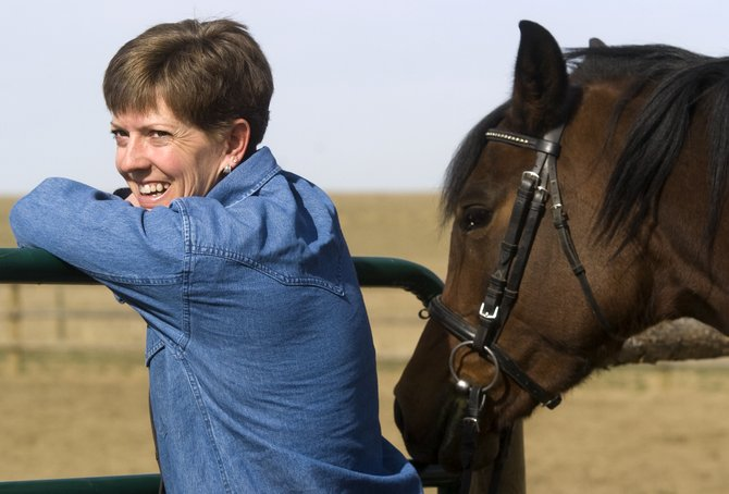 Medora Fralick smiles while watching her daughter Ryan (not pictured) ride one of her Arabian horses in an arena at her home near Hayden on Friday afternoon.