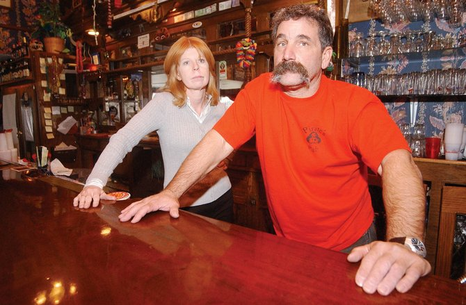 Jade Summit restaurant and Pirate's Pub owner Kevin Nerney, pictured Monday with his wife, Kathy, says liquor sales comprise about 50 percent of the business. Kevin Nerney said he is in the process of appealing the city's decision to revoke his liquor license. For the time being, Nerney has had to remove open containers of alcohol from the bar.