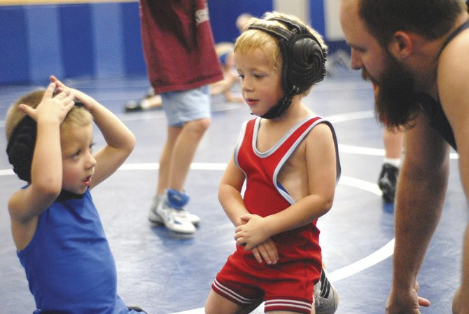 Holden Beckett, left, and Cody Baker, middle, discuss the fundamentals of wrestling with assistant coach Nathan Lewis during Bad Dogs youth wrestling practice Tuesday.