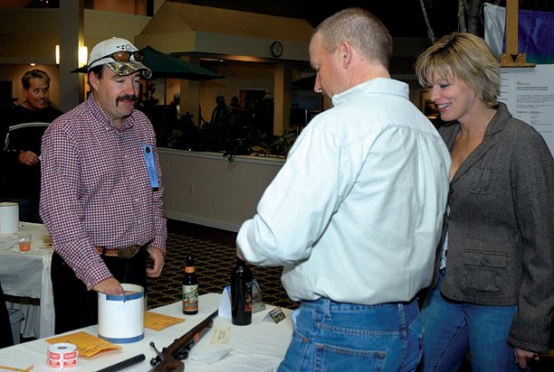 Vic Updike, left, takes a bid from Jeff Knights, center, and Amy Knights at last year's Ducks Unlimited banquet at the Craig Holiday Inn. This year's event is Saturday at the Craig Holiday Inn.
