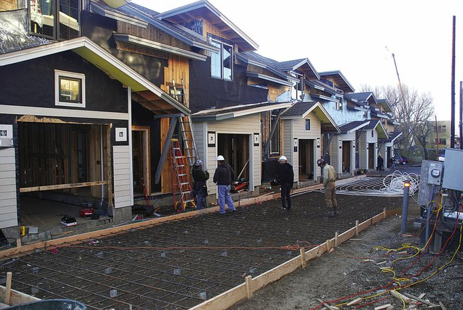 Construction crews install a snowmelt system Wednesday in the public alley that separates the Alpen Glow townhomes and condominiums just off Sixth Street.