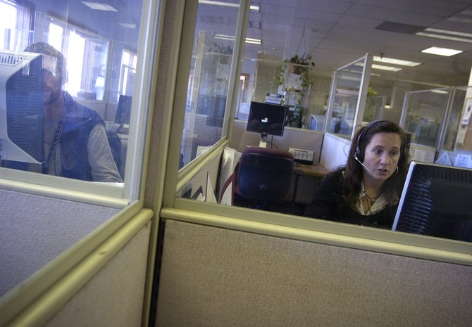 Reservations agents Michelle Petix, right, and Mark Hokanson answer calls at the Steamboat Central Reservations office on Pine Grove Road in Steamboat Springs on Nov. 8. Overall reservations for Steamboat Springs winter resort and lodging properties are slightly down from last year.