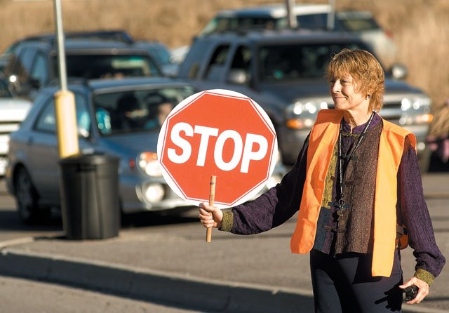 Crossing guard Beth Bagley stops traffic during the after school rush on the Strawberry Park campus Thursday afternoon. School district officials have hired consultants to evaluate traffic flow and parking for the area, which is shared by the elementary and middle schools.