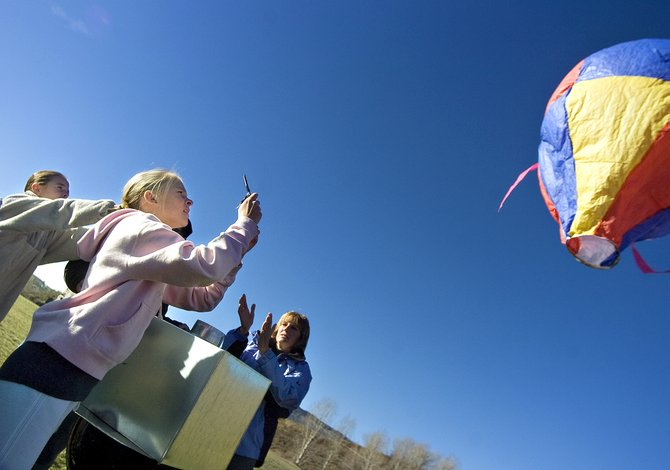 Emma Wilson snaps a picture of her hot air balloon as it flies away outside Steamboat Springs Middle School on Friday morning. Wilson built the balloon with her partner Meg O'Connell, far left.