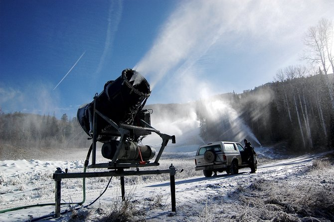 Snowmaker Mike Bentley jumps out of his Steamboat Ski Area vehicle earlier this week to check one of the dozens of guns set up along the Vagabond trail at the Steamboat Ski Area. Snowmakers are hoping for cooler temperatures this week in order to make snow at the resort - which has delayed its opening to Nov. 30.
