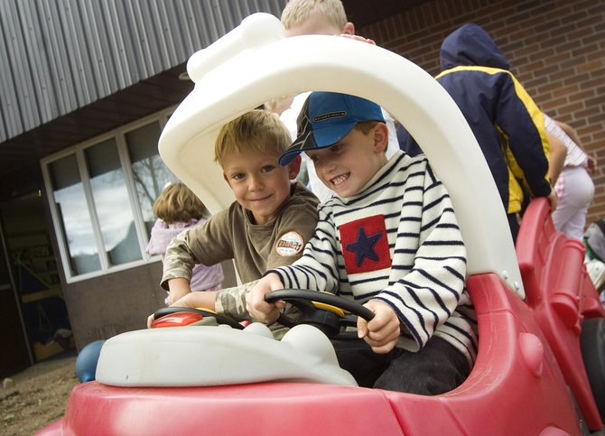 Kindergartners Jack Colfer, left, and Kevin Kaster play in a toy car on the playground at Soda Creek Elementary School on Friday.