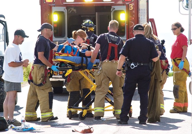 Katherine Ingalls is moved to a waiting ambulance by members of Steamboat Springs Fire Rescue after a collision between the cyclist and a large tractor-trailer southbound on Routt County Road 129 outside Steamboat Springs on June 29.