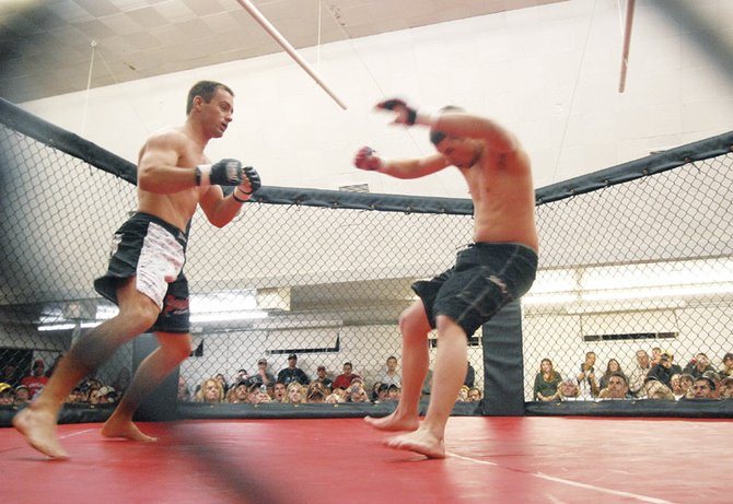 Travis Linsacum, left, delivers a blow to Carl Futch in the first round Saturday. Linsacum won the fight by knock out.