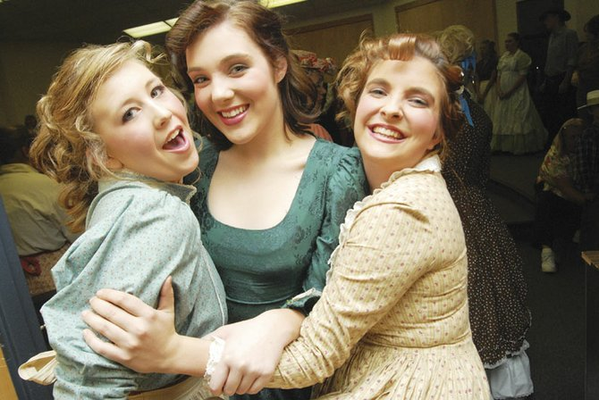 "Emily Hepworth, left, Emily Norris and Tanya Rinehart strike a pose during vocal warm-ups on the opening night of the musical, ""Oklahoma!"" The three seniors have been performing together on stage since they were freshmen."