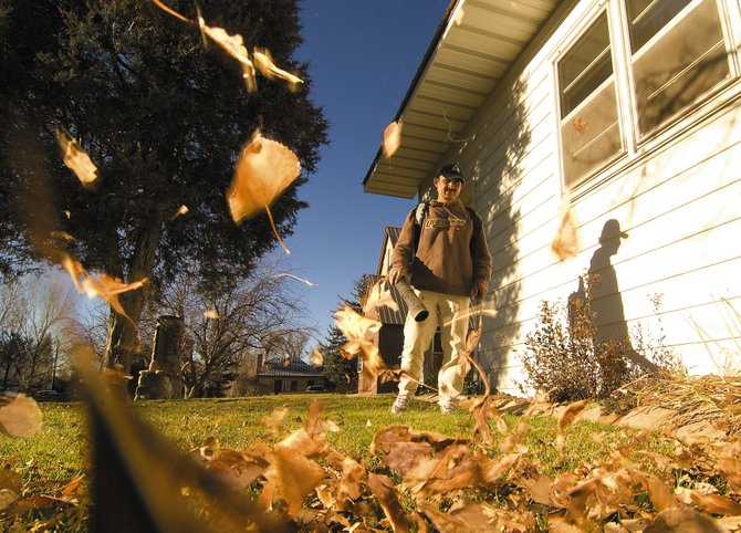 Aquiles Ricardez, of Kinnikinnick Lawn and Garden, blows leaves out of the front yard of the Holy Name Catholic Church on Oak Street. It might have been the perfect day to finish up those last-minute chores, because weather forecasters expect Monday's high temperatures to disappear by the end of the week.
