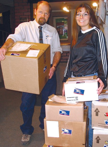 Jim Stoddard, owner of PackCenter Shipping, stands with office manager Sarah Gillroy, next to packages ready to be shipped overseas to troops with APO addresses in Febuary. Donations from the public help to pay for shipping the packages to men and women in uniform stationed overseas.