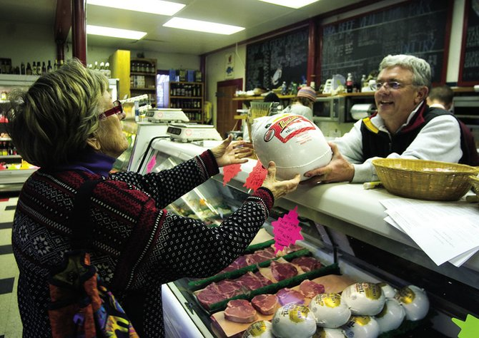 Birthe Wiik, left, picks up her family's Thanksgiving turkey from Bill Hamil, right, at the Steamboat Meat & Seafood Co. on Wednesday. The Meat & Seafood Co., as well as area grocery stores, will be open today to help shoppers with their last-minute Thanksgiving meal needs.