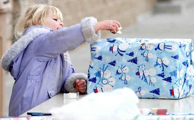 Michelle Debowes, 5, puts a ribbon on the top of a freshly wrapped gift Friday in front of Wal-Mart. Debowes was helping members of First Christian Church with a fundraiser during Black Friday.