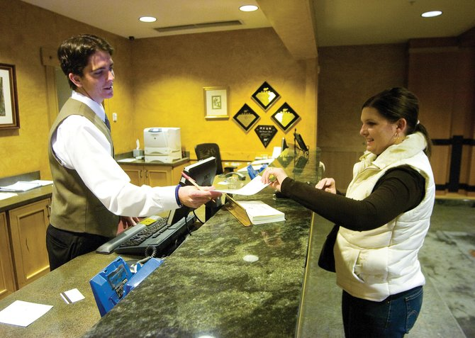 Steamboat Grand Resort Hotel employee Kyle St. John, left, helps visitor Sharynne Wilson check in to the hotel Wednesday afternoon. Area lodging properties are expecting about 3,000 visitors Saturday night, a decrease in numbers from the corresponding weekend in 2006.