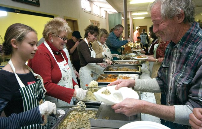 Claire Cox, left, and her mom, Kathy, second from left, serve a Thanksgiving meal to Bruce Kleiman during the annual community dinner at the Holy Name Catholic Church in Steamboat Springs on Thursday afternoon.