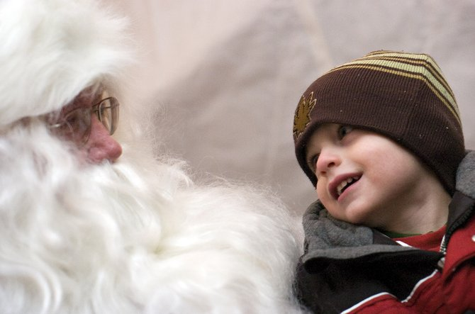 "Dylan Johnston, 3, gets a good look at Santa Claus while delivering his Christmas wish list at the ""Light Up the Night"" community tree lighting ceremony Friday Routt County Courthouse lawn in Steamboat Springs."