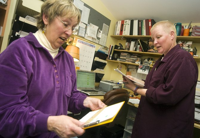 Liz Croes, left, and Jax Larsen, right, compare driver lists in the Alpine Taxi offices in Steamboat Springs on Friday. Alpine Taxi could see a higher demand for service this winter because of staff shortages and cut bus routes at Steamboat Springs Transit.