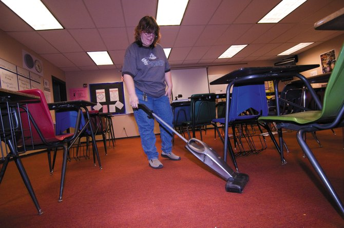 Custodian Christine Bark vacuums a classroom at the Steamboat Springs Middle School on Tuesday afternoon. The Steamboat Springs School District is facing a shortage of custodial staff in many of the schools. As a result, the district has hired students and teachers to fill the void in the after-school hours.