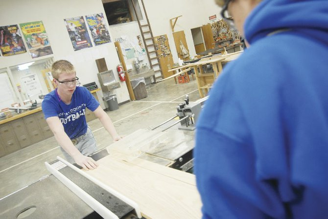 Jarrod Stillion, left, and Tayna Letamendi cut the base of the cookbook stands they sold. The money they raised selling the stands goes back into the program. As an incentive, the students earn a portion of the money they raised.