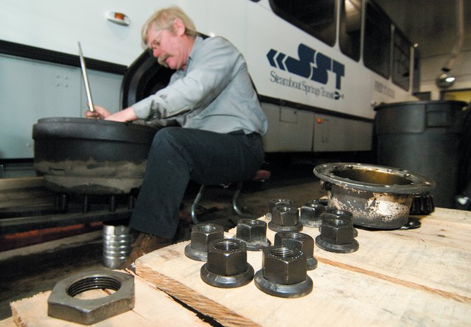 Bus mechanic Thomas Zurstadt works on the front wheel of a city bus Monday morning at the transportation center. The Transportation Department is expected to undergo a transition this year as longtime director George Krawzoff steps down after being appointed to the Colorado Transportation Commission. Krawzoff will resign after this winter to avoid any conflicts of interests.