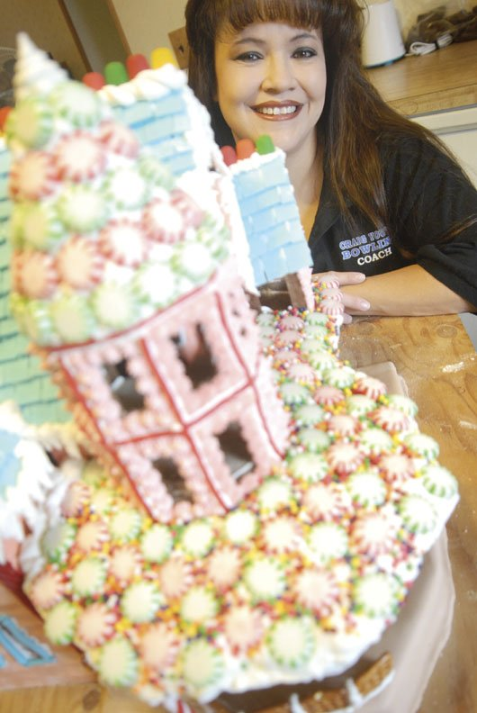 Shirley Cromer with the gingerbread house she's built for the Downtown Business Association's fourth annual gingerbread house contest.  This is Cromer's first attempt at a gingerbread house, spending the past three weeks putting her house together.