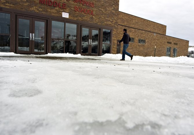 Bill Stewart makes his way across icy sidewalks at the entrance to Steamboat Springs Middle School on Tuesday afternoon.  The sidewalks are one of several issues that could be resolved with potential additional funding to the school by the Education Fund Board.