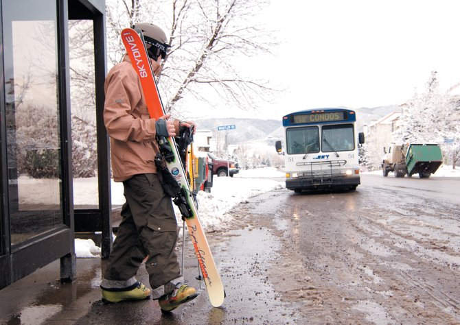 Skier Ryan Richard waits for a bus along Walton Creek Road on Thursday morning. The city of Steamboat Springs is restoring service to three bus routes later this month. The routes were cut earlier this year because of a shortage of drivers.