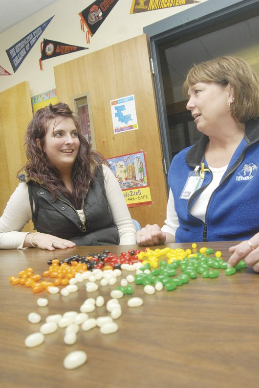 Tanya Rinehart, left, a Moffat County High School senior, talks with Carroll Morris, MCHS counselor, Friday afternoon at the school. Morris has started a Tolerance Group, suggested by Rinehart, at the high school to teach students to look past others' dress and hairstyles, which are illustrated by the jellybeans she uses that look like a certain flavor but are made to taste like another color.