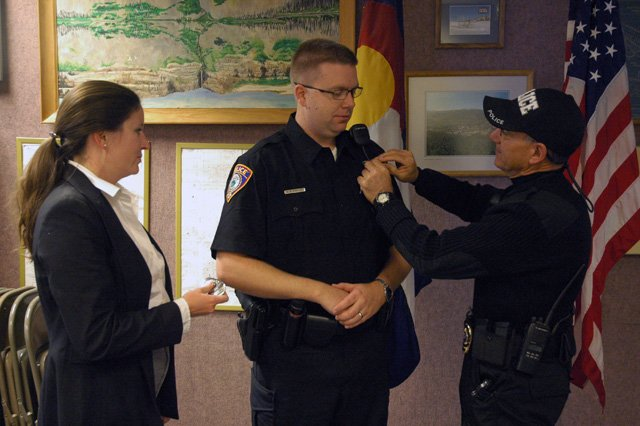 Oak Creek Police Officer Erik Foster, center, is promoted to the rank of sergeant by Police Chief Russ Caterinicchio on Tuesday. Foster's wife, Julie, holds his old officer badge.