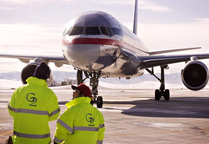 Casey Nelson, left, and Chris Anthony share a word as the first American Airlines flight of the season taxis into position for deplaning on the tarmac at  Yampa Valley Regional Airport on Thursday afternoon.
