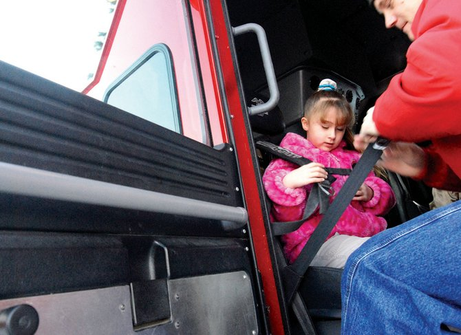 K.C. Hume straps Alissa Flannery, a third-grader at Ridgeview Elementary, into the fire engine for a ride to school after the Substance Abuse Prevention Program's award ceremony Thursday morning at McDonald's in Craig. Students were awarded money for tickets they sold to a pancake breakfast that raised about $6,900 to benefit the SAPP program.