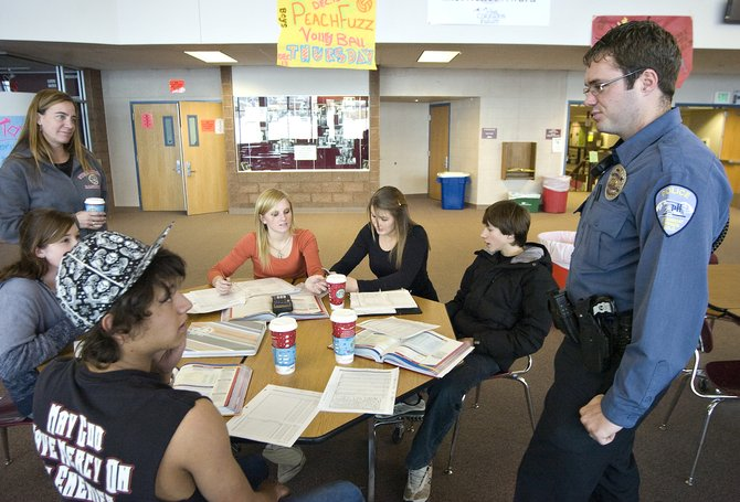 Chase Rippa, bottom left, and several other Steamboat Springs High School students visit with Officer Josh Carrell, far right, in the commons area at the high school on Friday afternoon. Carrell has recently taken over the School Resource Officer position from Deb Funston, top left.