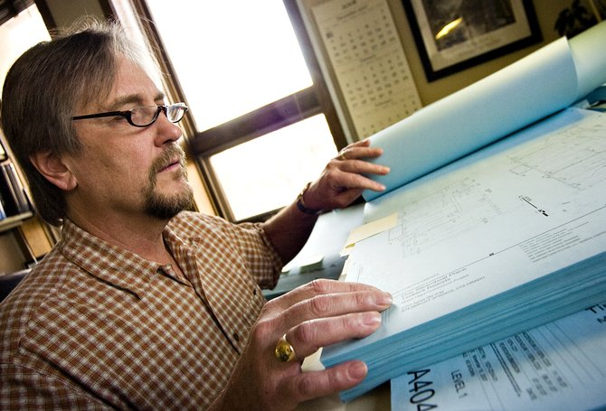 Ted Allen looks over a series of plans for the One Steamboat Place development at his office in the Routt County Regional Building Department in Steamboat Springs on Tuesday afternoon.