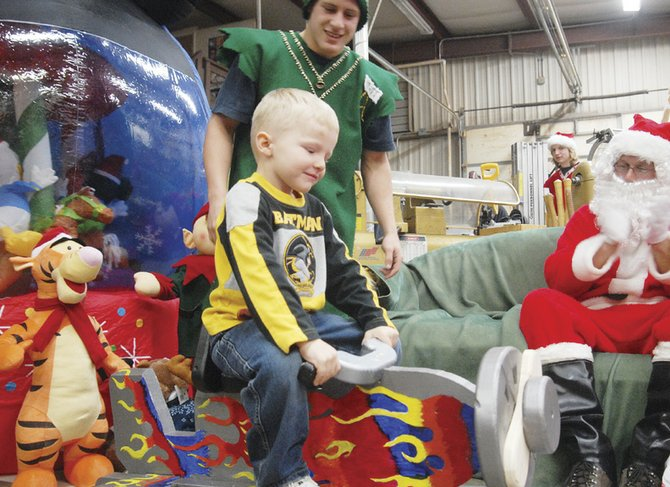 Logan Flint, 5, tries out his airplane, made by Matt Kincheloe, at Santa's Workshop on Wednesday in the Moffat County High School woodshop. Members of the high school's woodshop class dressed up as elves and gave handmade toys to area children.