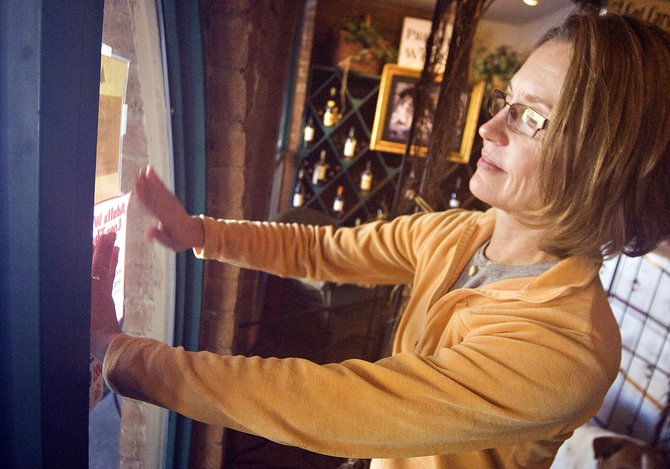 Kay Stuart, owner of the Market on the Mountain shop in Steamboat Springs, places a sign in her front window reminding patrons that it is unlawful and irresponsible to purchase alcohol on behalf of underage persons.