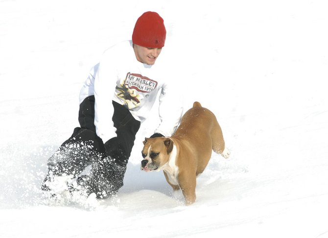 Nick Doolin tackles his dog Jetta at North Park on Thursday in Craig. Three to six inches of snow are expected by 6 p.m. today with possible snow falling throughout the weekend.