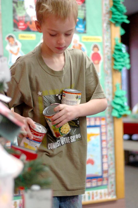 Cole White drops off canned food Thursday morning in Michele Conroy's class at Sunset Elementary. The second-grade class collected more than 40 items, including cans of peas and noodles.