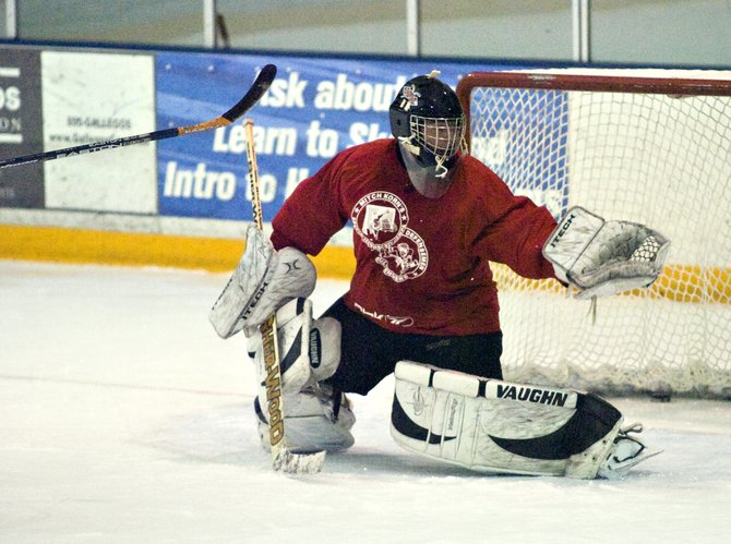 Goalie Jeff Dawes stops a shot on goal during hockey practice at the Howelsen Ice Arena on Thursday afternoon.