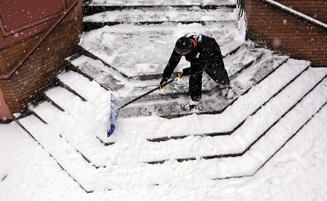 Aurdio Barroza of John's Construction shovels snow off the stairs of Old Town Square in Steamboat Springs on Thursday afternoon. Keeping the stairs cleared was a full-time job as a steady stream of snow fell from the sky as Barroza continued to shovel.