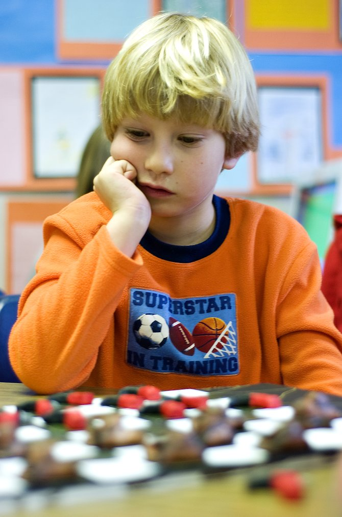 Soda Creek Elementary School third-grader Elijah Austin ponders his next move in a game of checkers during class Friday afternoon. Austin made the unique western-themed checkers set on his own during a lesson about pioneer children making their own toys.