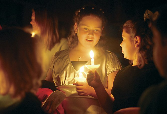 Emily, left, and Abigail Lincke proceed out of First Congregational United Church of Christ on Monday. The candles were part of the church's Christmas Eve Candle Light Service.