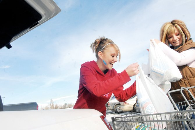 Tasha, left, and Barbara Burnett load Christmas gifts into the trunk of their car Monday at Wal-Mart. The Burnetts were among many shoppers picking up last-minute presents before the holiday.