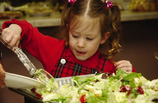 Five-year-old Miranda Cantele helps her father, Mitch Cantele of RE/MAX Steamboat (not pictured), serve salad during the Steamboat Springs Board of Realtors Community Christmas Dinner on Tuesday at Holy Name Catholic Church.