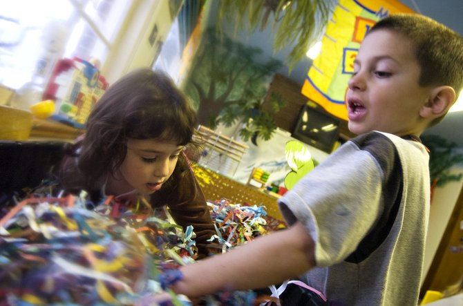 Mikey Buccino, right, and Makayla Kueber play in a bin of shredded paper at the Laurel Street School in Steamboat Springs on Thursday afternoon.