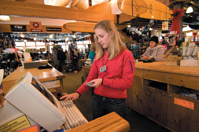 Ski Haus employee Arlie Chapman rings up a post-Christmas sale at a local outdoor store earlier this week while customer Diane Glover waits in the background. Business was steady after the holidays, bringing smiles to the faces of retailers looking for a strong finish to 2007.